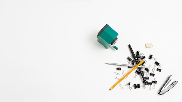 Office stationery tools randomly scattered in heap on white background, flat lay