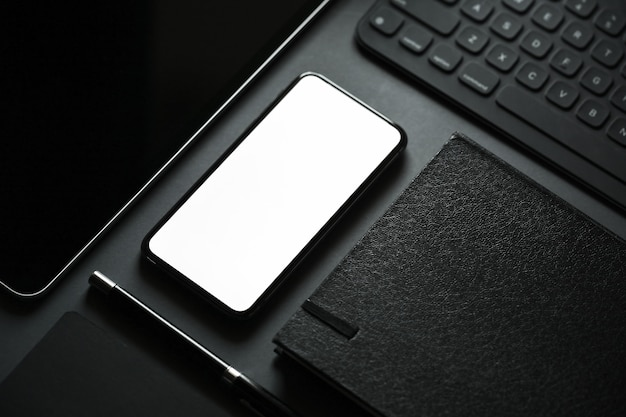 Office stationery with blank screen mobile smart phone on dark background.