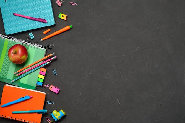 Office and student supplies on black chalk