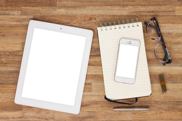 Рабочий стол в офисном стиле с белым планшетом, мобильным телефоном и ноутбуком, вид сверху