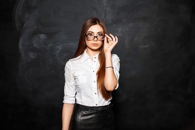 白いブラウスとスカートのオフィススタイリッシュな女の子がメガネを修正します