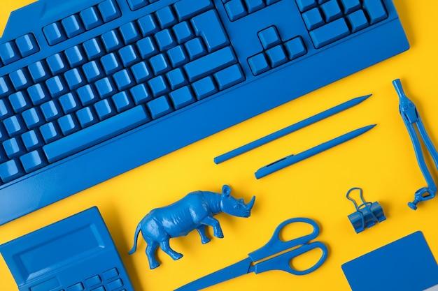 黄色の背景の上に古典的な青い色で描かれた事務用品