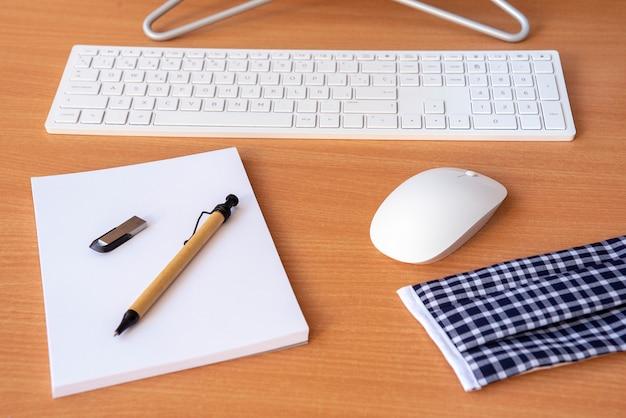 事務用品と机の上の防護マスク