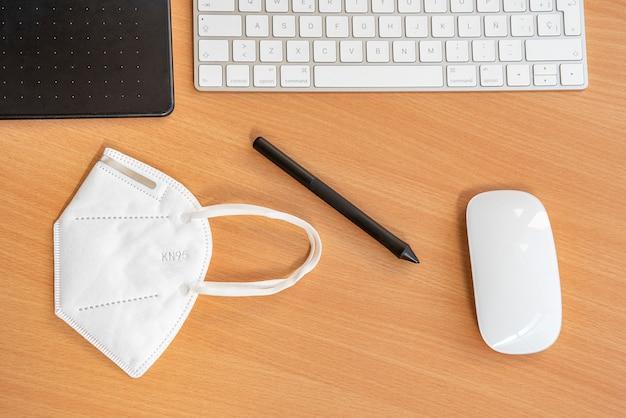 Канцелярские товары и защитная маска на столе