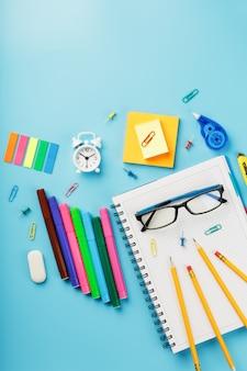 事務用品は青いテーブルの上にあり、自宅で自分の手で作業できます。