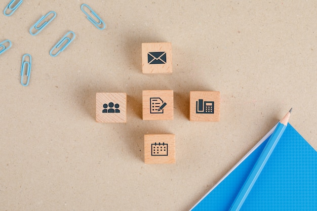 Office supplies concept with icons on wooden cubes, stationery set flat lay.