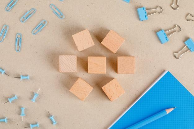 Concetto degli articoli per ufficio con i cubi di legno, le clip di carta e del raccoglitore, la matita, il taccuino, disposizione piana dei perni di spinta.