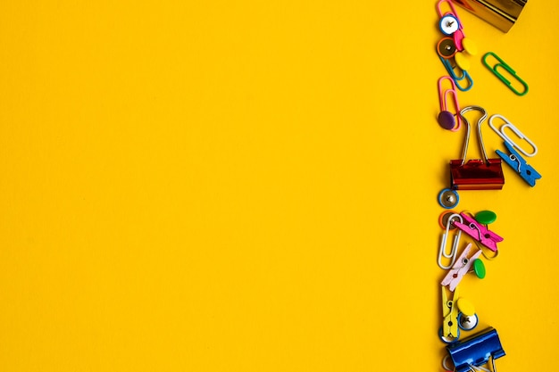 Office supplies in the form of colored buttons and paper clips