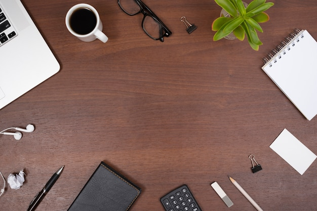 Office supplies; gadgets; cup of tea and plant with earphones on a wooden table