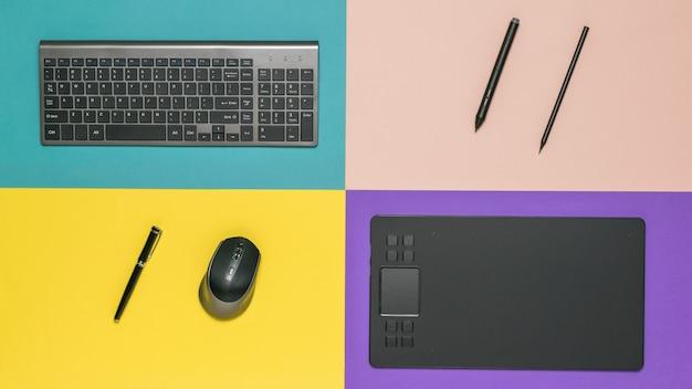 Канцелярские товары, клавиатура и графический планшет на разноцветном пространстве. периферийные устройства для компьютеров.