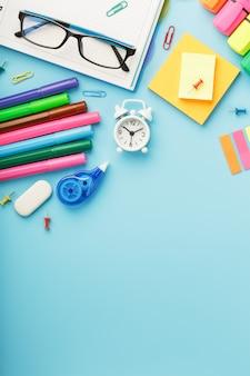 Канцелярские товары лежат на синем. учиться в школе. радужный цвет.