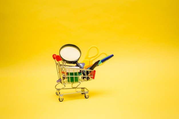 Office supplies in a metal cart on a yellow isolated background with a copy of the space
