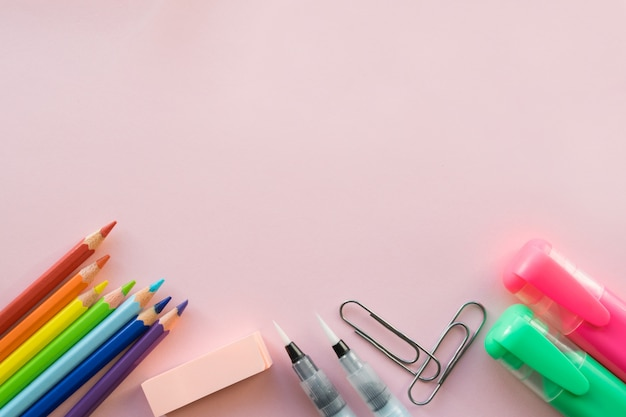 Office supplies on pink background. copyspace