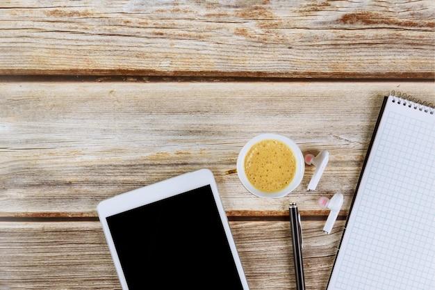 커피 컵 디지털 태블릿 무선 헤드폰으로 테이블에 사무 용품 나선형 메모장