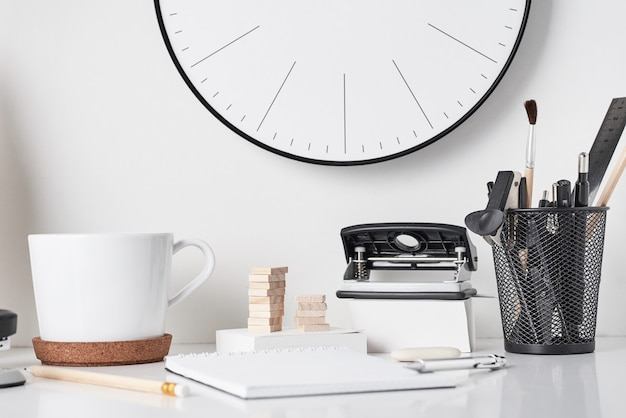 Office supplies and wall clock on white