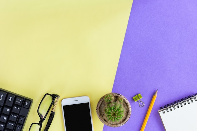 Office supplies on yellow and purple in top view