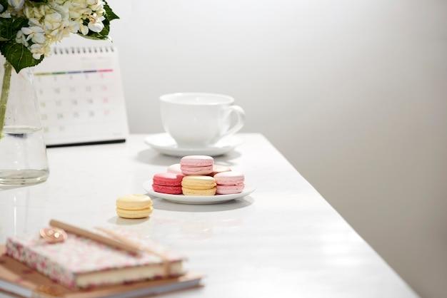オフィステーブルデスク。カレンダー、日記、オルテンシア ブーケ、マカロン、白のコーヒーが入った女性らしいデスク ワークスペース フレーム