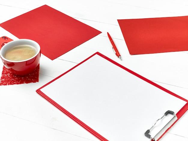 Стол офисный стол с набором красочных принадлежностей, белый пустой блокнот, чашка, ручка на белом.
