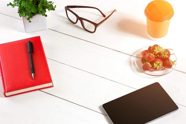 Office table desk with set of supplies, red notepad, cup, pen, tablet, glasses, flower on white background. top view and copy space for text. sun flare