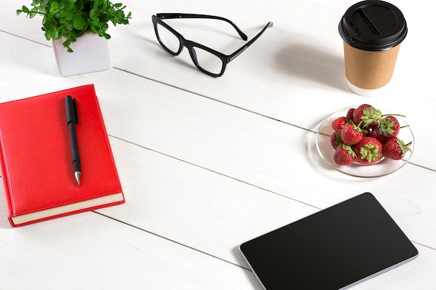 Office table desk with set of supplies, red notepad, cup, pen, tablet, glasses, flower on white background. top view and copy space for text