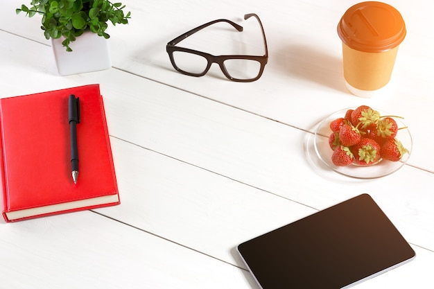 Office table desk with set of supplies red notepad cup pen tablet glasses flower on white background...