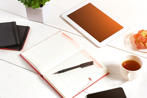 Office table desk with set of supplies white blank notepad cup pen tablet flower on white background...