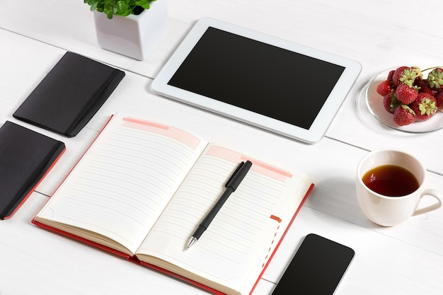 Office table desk with set of supplies white blank notepad cup pen tablet glasses flower on white ba...