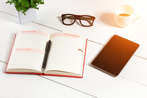 Office table desk with set of supplies, white blank notepad, cup, pen, tablet, glasses, flower on white background. top view and copy space for text. sun flare