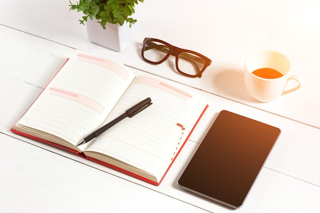 Office table desk with set of supplies, white blank notepad, cup, pen, tablet, glasses, flower on white background. top view and copy space for text