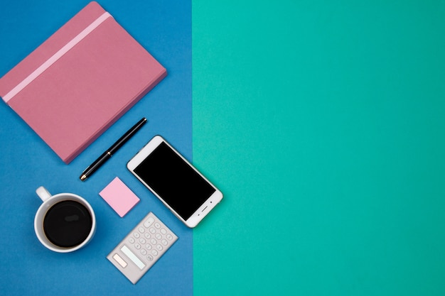 Office table desk with smartphone and other office supplies on green and blue background.