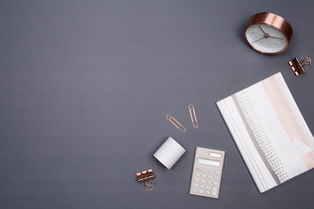 Office table desk with smartphone and other office supplies on grey background.