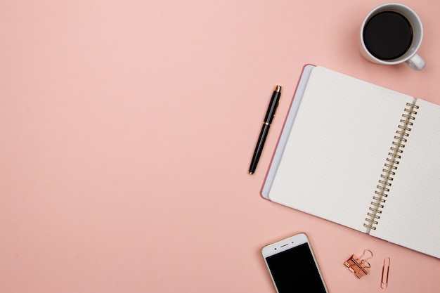 Office table desk with smartphone and other office supplies on pink background.