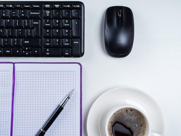 Офисный стол письменный. рабочее пространство с пустой записной книжкой, клавиатурой, канцелярскими принадлежностями и кофейной чашкой на белом фоне.
