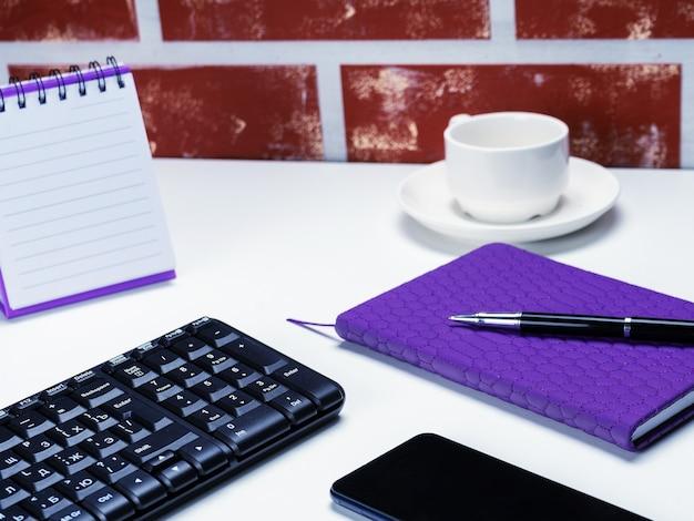 Офисный стол письменный. рабочее пространство с записной книжкой, клавиатурой, канцелярскими принадлежностями и чашкой кофе на белом фоне.