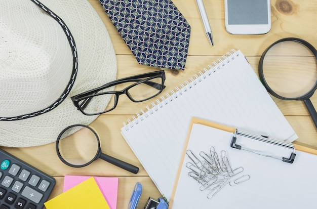 Office table top view with the glasses, note book, magnifying glass and mobile phone