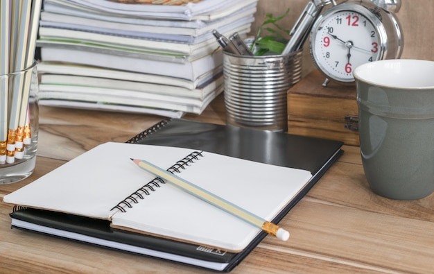 Office table with blank notebook, clock, coffee cup