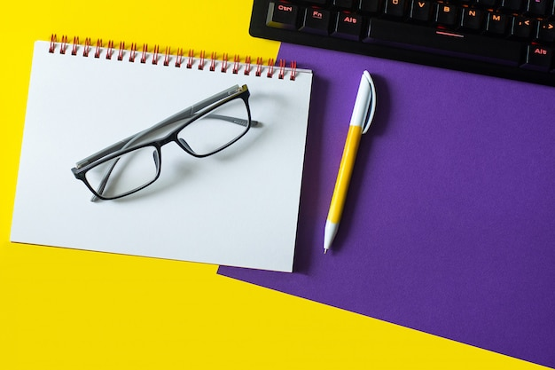 Office table with blank notebook and keyboard  and glasses.