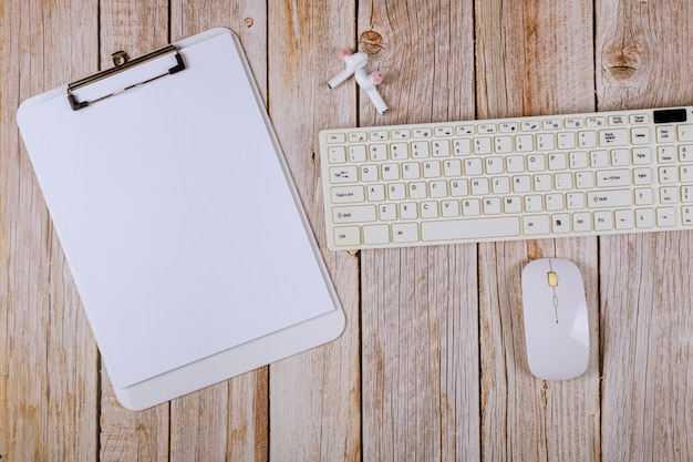 Office table with blank notebook and keyboard on a wooden table background.