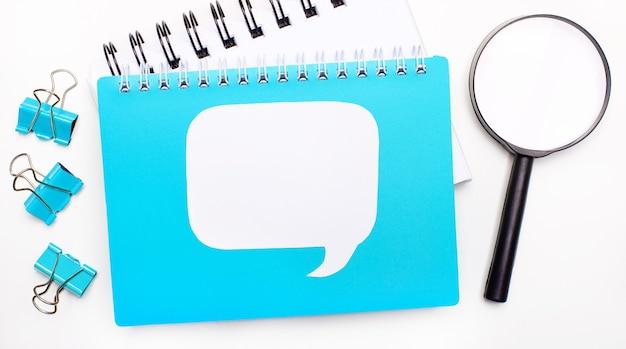 青いメモ帳、ペーパークリップ、虫眼鏡、テキストを挿入する場所のある白い空白のカードが付いたオフィステーブル。コピースペース、フラットレイの上面図。スタイリッシュなワークスペース