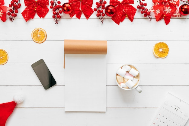 Office table with devices, supplies and christmas decor. view from above