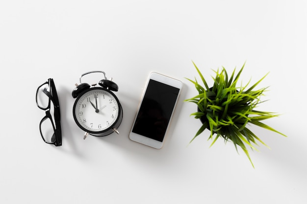 Office table with glasses, clock, phone and plant