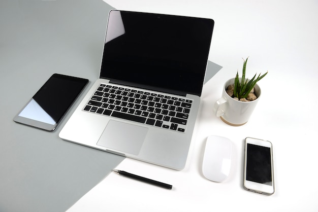 Office table with  laptop computer, notebook, digital tablet and smartphone on two tone ba