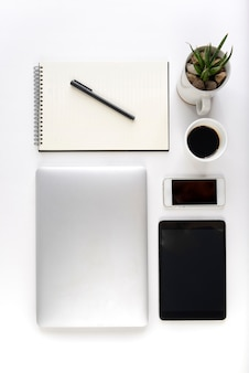 Office table with laptop computer, notebook, digital tablet and smartphone on white background.