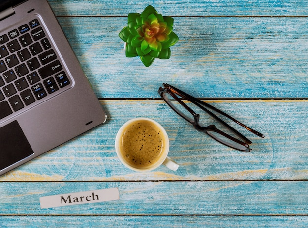 Office table with march month of calendar year, computer and coffee cup, glasses view