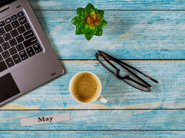 Office table with may month of calendar year, computer and coffee cup, glasses view