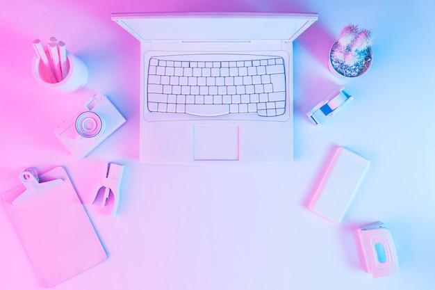 노트북 컴퓨터, 카메라 및 스마트 폰이있는 사무실 테이블은 활기찬 대담한 그라데이션 보라색과 파란색 홀로그램 색상 조명으로 흰색으로 칠해졌습니다. 컨셉 아트. 최소한의 사무실 초현실주의.