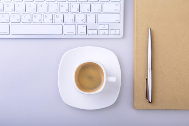 ノートブック、コンピューターのキーボード、一杯のコーヒー、タブレットpcのオフィスのテーブル。コピースペース。