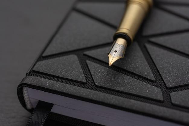 Стол офисный с блокнотом. перьевая ручка с черной ручкой ..