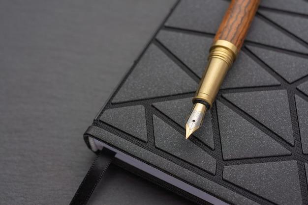 メモ帳付きのオフィステーブル。茶色のハンドルが付いた万年筆。