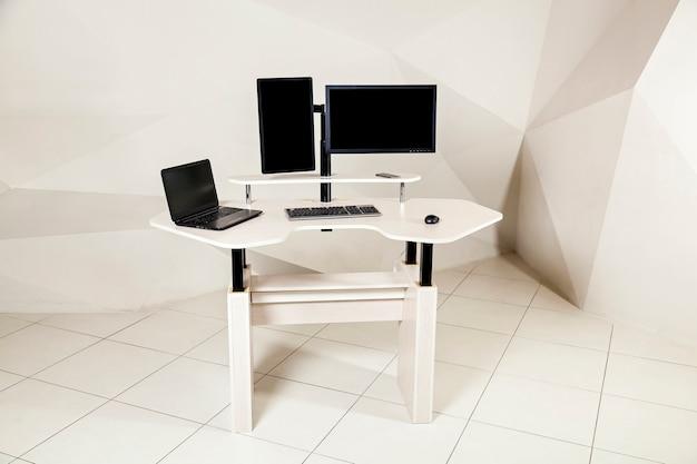 Office table with two monitors a lifting mechanism for the holder of a manitor and a table